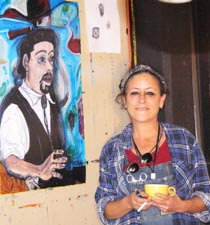 Tasha Robbins standing by her painting of Dave Bronks
